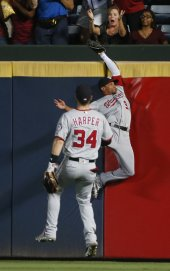 Washington Nationals center fielder Ben Revere (9) makes a catch at the wall on a ball hit by Atlanta Braves' Freddie Freeman in the fourth inning of a baseball game in Atlanta, Friday, Aug. 19, 2016. Nationals right fielder Bryce Harper (34) looks on. (AP Photo/John Bazemore)