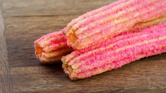 PIXAR FEST FOODS AT DISNEYLAND RESORT (ANAHEIM, Calif.) ñ Pixar Fest, the biggest theme park celebration of beloved stories and characters from Pixar Animation Studios, is coming to the Disneyland Resort April 13 through Sept. 3, 2018. Favorite Pixar pals and stories are inspiring delicious treats, such as this strawberry churro in Tomorrowland at Disneyland park. (Disneyland Resort)